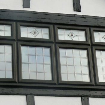 Black uPVC windows with lead details and decorative glass