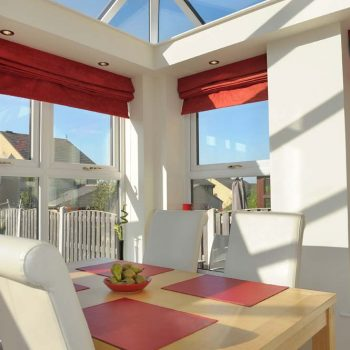 Internal view of orangery installation showing dining area and glass roof