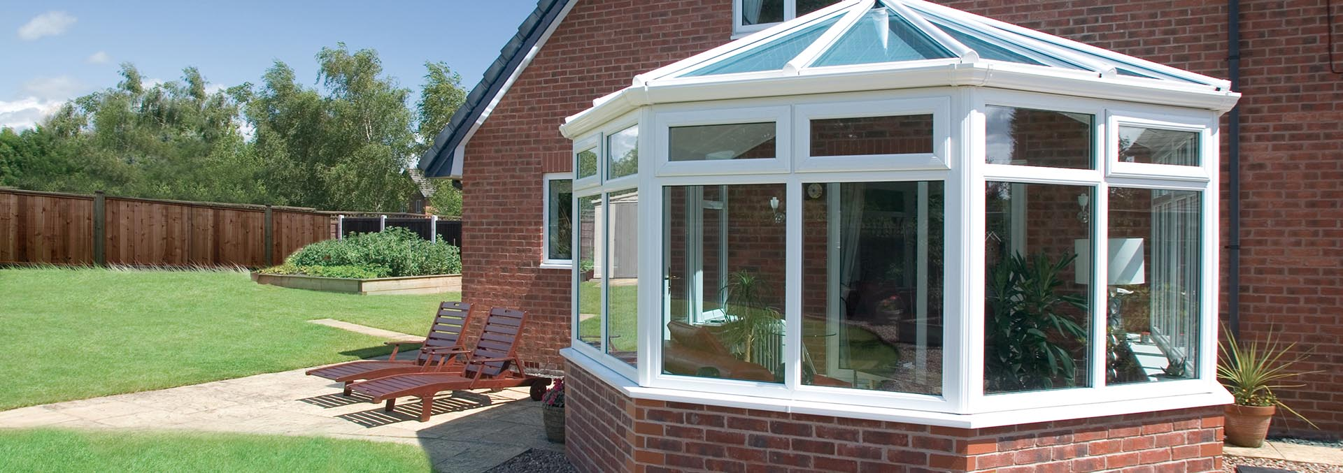 Small victorian conservatory with uPVC frame and brick base