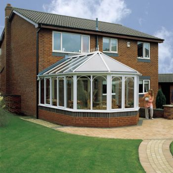 Conservatory installation, built with white upvc profile and a brick base